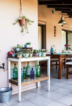 Galería en tono siena con vetas rosadas, botellas recicladas y suculentas que crean una atmósfera de romanticismo agreste en la casa de la decoradora Vero Palazzo.