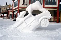 Two polar bears made of snow are shown stranded atop a big SUV in this snow sculpture