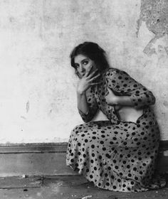 Francesca Woodman - crouched position, figures over part of fave looking into the lens other hand holding body