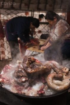 """Chinese Mongolian lamb castration and mark in the sheep ear. Mongolian housewife cook lamb and sheep offal preparation for lunch celebrate to the """"lamb castration holiday"""" in the yurts. Hulunbeier grassland, Inner Mongolia Autonomous Region, China,May 21, 2011."""