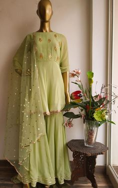 Golden Gota Patti floral motifs sprinkled all-over the bodice Three-quarter sleeves Boat neck with pintucks detailing in the centre front A-line short Kurti Pattern with gota lace border with Sequinned Net Dupatta Sharara is in kalidar pattern with gota border
