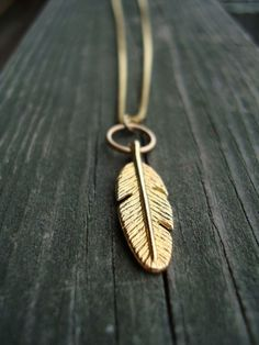 a simple gold feather pendant