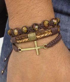Kit de pulseiras unissex composto de 3 pulseiras na cor marrom, sendo:  - 1 pulseira shambala confeccionada em macramê com cordão encerado na cor café e crucifixo em banho uro velho.  - 1 pulseira de couro trançado na cor marrom  - 1 pulseira shambala de cristais facetados    > Pulseiras ajustáve...