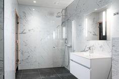Suuri laatta tekee tilasta yhtenäisen näköisen. Marmori on tällä hetkellä trendikäs materiaali ja tekee tästä kylpyhuoneesta suorastaan ylellisen oloisen.