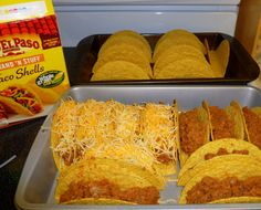 2 lb ground beef, onion diced, can diced green chilies,1 pkg taco seasoning, 8 oz can low sod tom sauce,16 oz can refried beans, 2 cups shredded cheese,20 hard taco shells Brown beef and onion.Drain off any excess liquid. Add chilies, refried beans, tomato sauce, and taco seasoning. Spoon meat mixture into shells. Stand up in 9X13 Baking dish. Sprinkle cheese into each shell. bake at 400 deg for 10-12 mins.