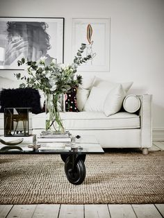 Hessian rug, glass coffee table on wheels and canvas couch.