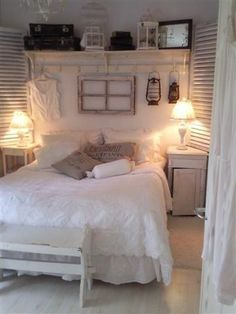 old window hangin over bed..on an peg white beadboard wall with lanterns and a piece of vintage clothing...kathymorin153 french cottage shabby chic home