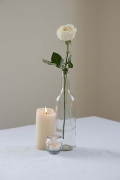 A single white rose and candles for a simple centrepiece #HoiAnEventsWeddings #VietnamBeachWeddings