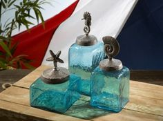 Our blue aqua glass Sea Life Canister Set is perfect for your coastal themed home. These textured-finish glass canisters feature decorative sea life tops with a circular design holding a starfish, a n
