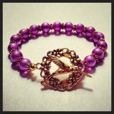 Spring 2013 Collection: Purple Hummingbird bracelet  made with purple glass beads, antiqued gold spacer beads and an antiqued gold hummingbird toggle clasp. $26.99