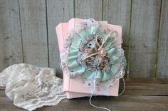 2 vintage books, hand painted soft pink, adorned with a lace heart filled with potpourri and tied with lace and pearls, the page edges of the books are painted white. Everything is permanently and fir