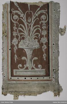KLM 39767:2. Tapet av papper. 2 st bitar. Målade tapetbitar i pompeijansk stil med övre delen av tapeten och delar av ett brunrött ramparti på högra sidan. Ornament i grisailles. Datering: Sengustaviansk stil, 1790-tal.