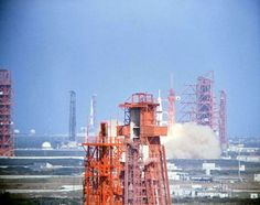 """for-all-mankind: """" Apollo 7 launching, with Apollo 8 on pad A in the background. The more commonly-known image of Apollo 7's launch has the vehicle in the background, too, but is obscured by the..."""