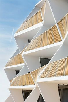 This Australian building features a very sculptural facade. It's a series of terraces built with sharp angles on each floor and they form a geometric pattern. The wooden railings also emphasize the unique forms.