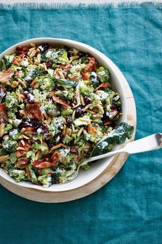 Cranberry-Almond Broccoli Salad | Broccoli salad is usually drowning in a creamy, often very sweet, dressing and studded with 1/2 pound crumbled bacon, making it more about the creamy dressing and bacon than about the actual broccoli. Ours uses a combination of canola mayonnaise and Greek yogurt to keep the calories in check. We opt for center-cut bacon (a bit less of it) and swap the usual raisins for lower-sugar dried cranberries to pack a subtle punch of tart.