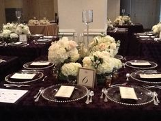 Gorgeous wedding centerpieces of white hydrangea, blush roses, and white garden flowers arranged in various sized vases surrounding tall candle holders!