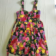 """Summer Vaca Sale!"" Sequin Hearts Sundress This floral-patterned sundress by sequin hearts is a size 9. The shell is made of 97% cotton and 3% spandex the lining is made of 100% polyester. It measures 36 inches long , 15 inches across the waist and 17 inches across the bust. It is a super stretchy material and has a padded bra area. It also features a bow tie and zips up the back with a ruffle trim just under bottom of the dress. Pleated. Sequin Hearts Dresses"