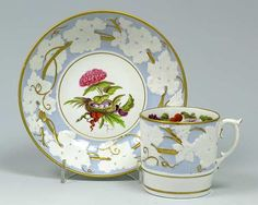A Miles Mason can and saucer with spur handle decorated with a moulded vine border on a blue ground, a painted bird's nest and flowers and fruit in the centre and inside the rim of the can