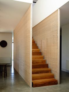 Wood stairs with wicker surround at the Torquay House in Victoria, Australia designed by Wolveridge Architects