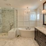 Love the chandelier and tub, wainscoting, glass shower with bench, as well as the dark cabinets against white background.