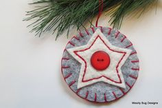 This wool felt ornament is made of a wonderful gray heather wool felt blend with a soft all natural cotton batting star. A wonderful bright red