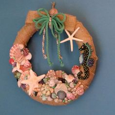 Gorgeous burlap beach wreath with seashells and seahorse. The burlap wreath is topped with a burlap bow and cording in seafoam green and multi colored off white that has touches of teal and brown in it. I added a nice sundial shell and an olive shell to the bow. the seahorse is