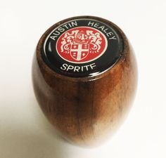 This is a Austin Healey Sprite Crested Wood gear shift knob. Fits ALL Sprites. You're not going to throw any random knob in your Sprite. This knob will be a natural fit for you and is made of elegant walnut wood. with a medallion displaying the proper Austin Healey Sprite logo .The shift knob is designed with a hard plastic insert that accommodates a range of shift lever sizes and thread widths. Prior to installing the shift knob, screwing on a jam nut is recommended. Makes a great gift!