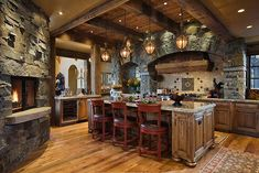 Rustic kitchen designed by Locati Interiors, Bozeman MT.  Decorative pendants, red barstool, kitchen stone fireplace, wood floors in kitchen, wood plank ceiling,