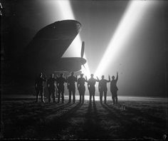 V-E Day! Ground crew on a RAF Bomber Command station in Britain return the 'V for Victory' sign to a neighboring searchlight crew. Silhouetted is the nose of a Lancaster bomber. (Imperial War Museum)