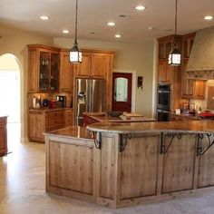 Kitchen Knotty Alder Cabinets Design, I love the stain and the wrought iron bar supports.
