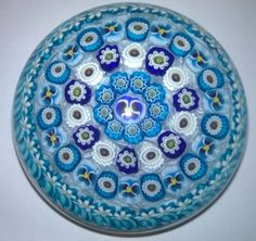Parabelle Glass 1997 concentric millefiori weight with circlets of cog, edelweiss, pastry mold and pansy canes, in turquoise, cobalt blue, yellow and white, around a central cobalt blue pansy, on a white lace ground. Signed and dated. Limited edition of 10. Diameter 3 www.theglassgallery.com