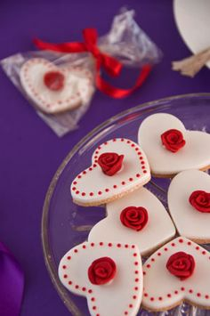 'Red rose' wedding cookies. Vanilla cookies coated with royal icing and decorated with handmade sugar roses. Individually wrapped in clear bags and tied with a ribbon.