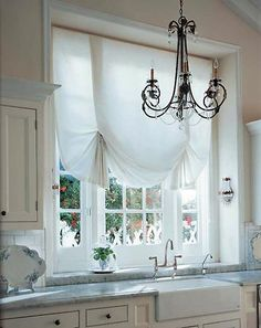 A Roman shade by any other name still looks really sweet! A lovely London style shade frames this kitchen window brilliantly.