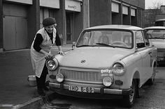 Old woman cleaning a Trabi, 1991
