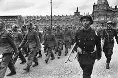 Liberation of Paris, 1944: French gendarmes march German prisoners off to captivity. In the absence of rifles, the gendarmes have pulled out their hunting side-by-sides. Their pistol holsters are empty, too.