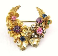 VintMiriam Haskell crescent multi color rhinestone brooch. Signed Miriam Haskell in an oval cartouche on the filigree back, which dates to the 1950s. Measures 1 3/4 inches tall by 1 3/4 inches wide. Gold tone. This brooch features a crescent design with a bouquet of gold tone and rhinestone flowers. At the bottom of the crescent are three yellow heart shaped rhinestones. The colors of all the rhinestones are as follows - purple, pink, blue, green, light yellow and clear. There are seed…