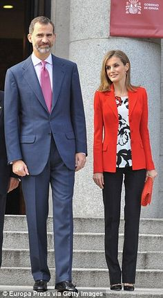 Pretty: Letizia steps out in an eye-catching red jacket, which went perfectly with her husband King Felipe's berry colored tie.