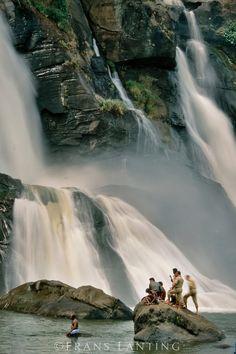 Men gathered at base of waterfalls, Trissur, Kerala, India