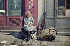 Fernand Cuville<br>  1917<br>  A young girl at play next to equipment and rifles in Reims, France.