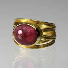 Captivating beauty! This Barbara Heinrich ring is a perfectly oversized statement of bold style. Handcrafted from 18K yellow gold, the criss cross band holds a bezel set oval rose colored tourmaline. What a style defining interpretation of the classic cocktail ring!Tourmaline = 5.56cttwBand tapers from 14 to 6.5mm wideStone measures 10 x 12.5mm wideSize 7.25