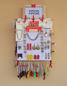 """Strawberry Crate Jewelry Display 1    Jewelry display made of fruit crate, cross stitch fabric, red rope,  wooden pegs and grill scewers.Additional sign """"hand made"""" is cross-stitched and framed."""
