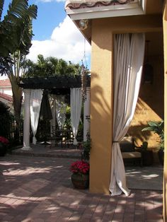 They added curtains later to the porch. $20.00 painter's tarps from Home Depot hung on iron curtain rods. Florida Tropical Bali/Moroccan Oasis