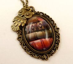 This nostalgic #necklace consists of a bronze-colored metal frame and a handcrafted glass cabochon with a beautiful motif with old books. Above the setting I have attached a... #etsy #jewelry #hairjewelry #earrings #dailyetsysales