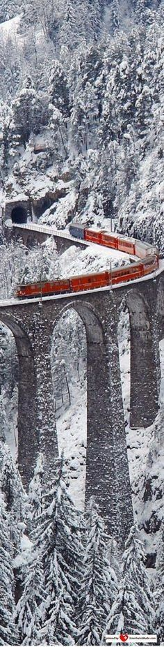 photo ... bright red train stands out on mountain trestle ... gray snowy landscape ...