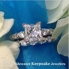 Contemporary ring with round brilliant diamonds showcasing a princess cut center diamond. Tidewater Keepsake Jewelers