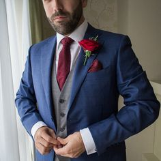 The Groom's Blue wedding suit with contrast grey waistcoat, burgundy tie and red rose boutonniere. Louise & Pete's Wedding at Glasson Country House Hotel. Groomswear by Louis Copeland & Sons. Photography by siobhanhennessy.com