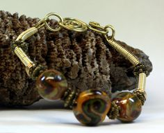 The beautiful Pecan Praline Lampwork Bead Bracelet is hand created with brass and brass colored craft wire, coiled brass colored craft wire, 3 beautiful lampwork beads in shades of caramel, tan, brown, yellow green, fine silver, brass colored accent beads, a hand created forged clasp. Fits up to a 7 3/4 inch wrist, jump rings can be added to make it fit a larger wrist. This will be a gorgeous handcrafted bracelet to add to your jewelry collection.