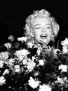 """Marilyn Monroe with a large bouquet of flowers from fans in Tokyo, 1954. """