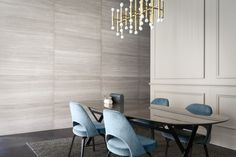 stunning grey dining room, luxe blue chairs, and insane gold lighting structure. ©Studiopepe