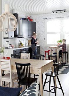 Riikka-Mari ja Vilma jutustelevat keittiössä. Petra-keittiöiden kaapistot antavat huoneelle särmää. Lisää ilmettä tuovat Secto Designin Octo-valaisin, Ykstuuman puusepän tekemä pöytä ja Design House Stockholmin sekä Ristomatti Ratian Saaristo-sarjan tuolit.